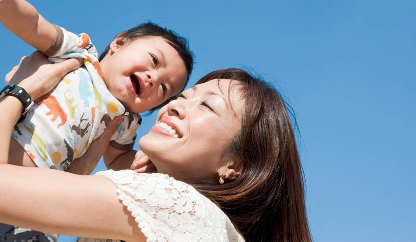 Asian woman holding a baby up in the air.