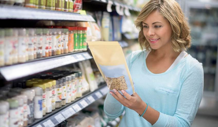 Woman in a grocery store looking at a bag of food.