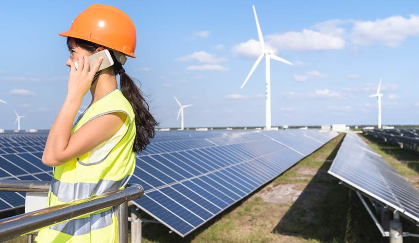Woman talking on a cell phone near solar panels and wind turbines.