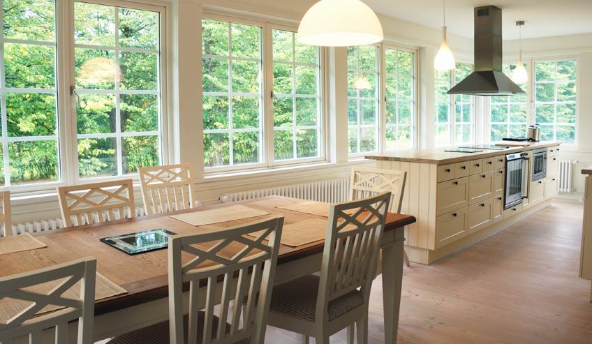 Bright, white kitchen with large windows.