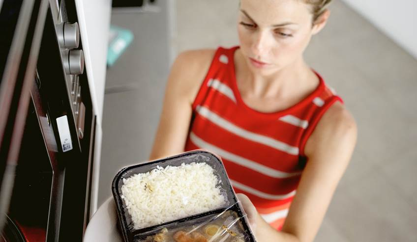 Woman pulling a food item from a microwave with flexible packaging.