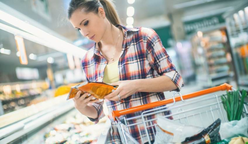 Woman in a grocery store looking at something packed with flexible packaging.