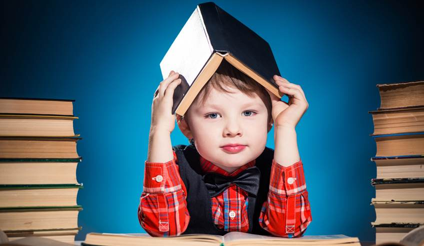 Little boy sitting with stacks of books with one over his head.