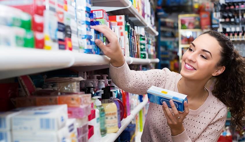 Lady reaching on a store shelf with many small boxes of product on it.