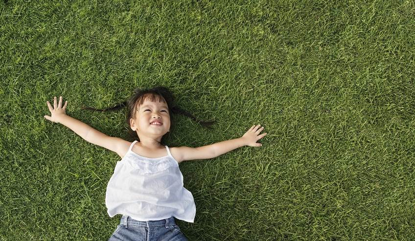 Happy little girl laying in the grass.
