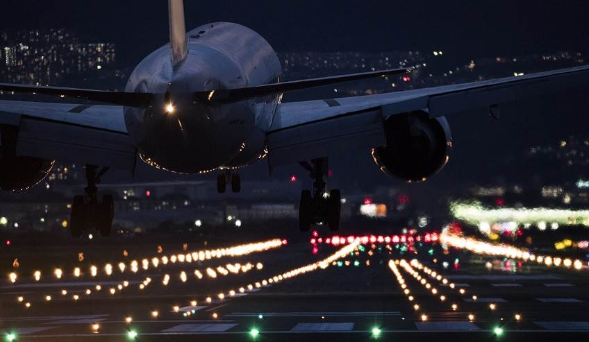 Airplane landing at night guided by runway lights.