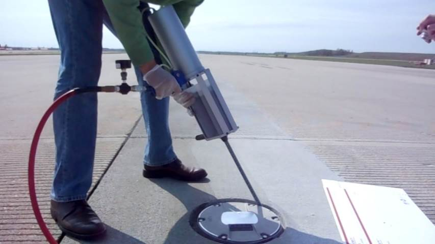 Person installing a runway light with sealant.