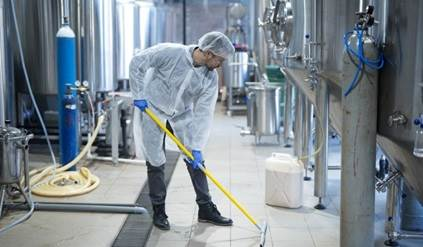 Industrial worker cleaning floor