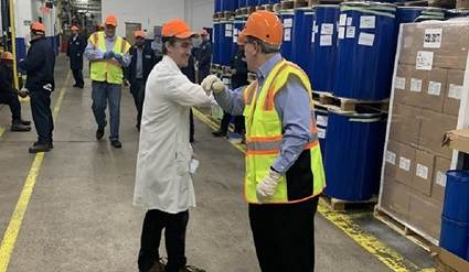 H.B. Fuller CEO Jim Owens handing out Foster disinfectant to employees.
