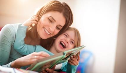 Woman and child reading a book and laughing