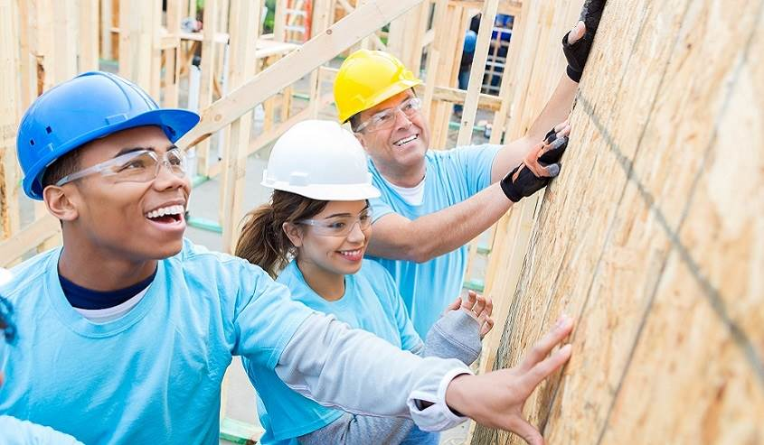 Corporate volunteers show community commitment working together to build a home.