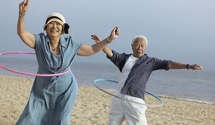 An active Asian couple doing hula hoops on the beach.
