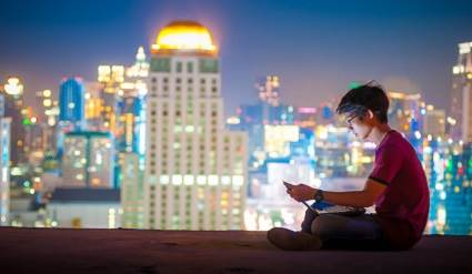 Boy on a laptop computer with a city skyline in the background.