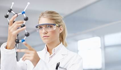 Woman holding a molecule structure in a lab coat.