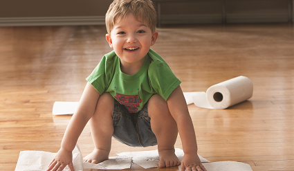 Little boy on the floor with paper towel unraveling in the background.