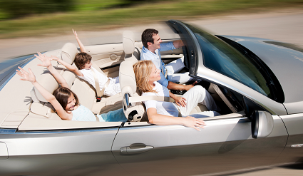 Family driving in a convertible with the top down.