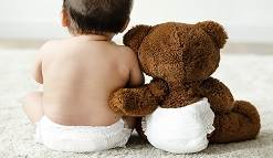 Baby and teddy bear in diapers.