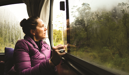 Woman looking out a window of an RV in the rain.