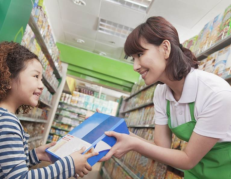 Little girl and clerk in a grocery store holding a box enhanced using Clean Melt packaging adhesive from H.B. Fuller