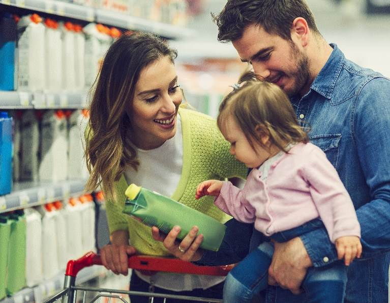 Family in a grocery store looking at a packaged item manufactured with Open Sesame technology.