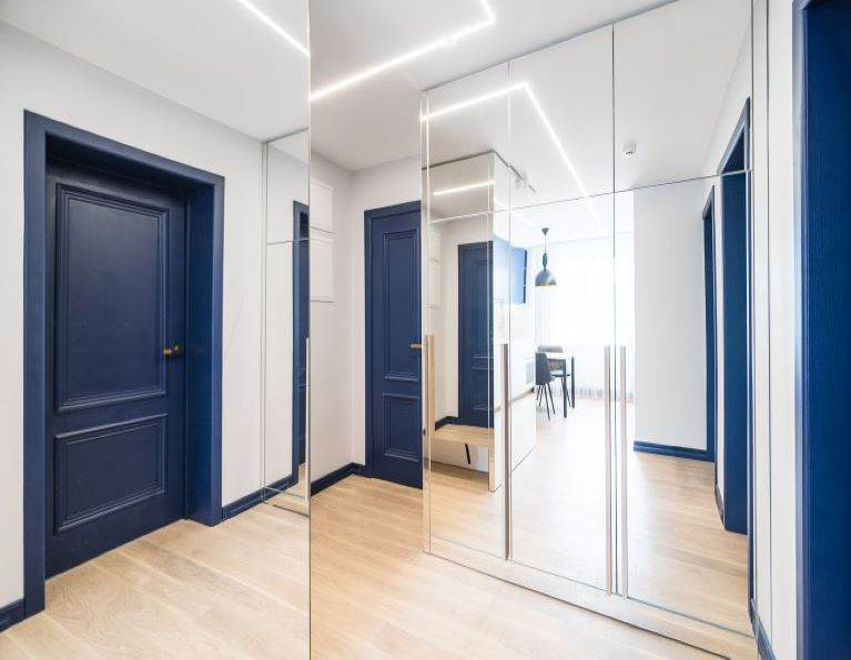 Apartment entryway with mirrors and a blue door