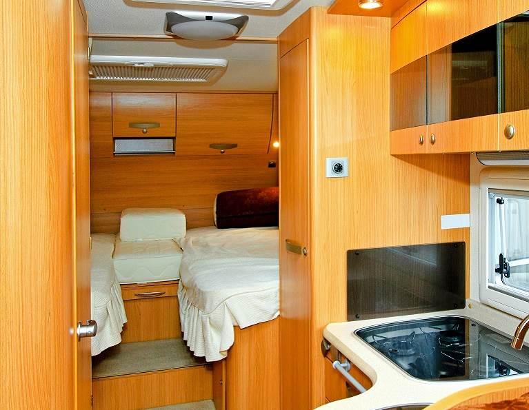 Inside of an RV with wood paneling, doors and cabinets.