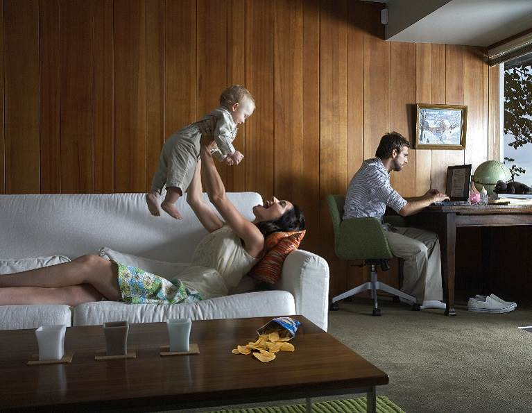 Family in a living room with wood panels on the walls.