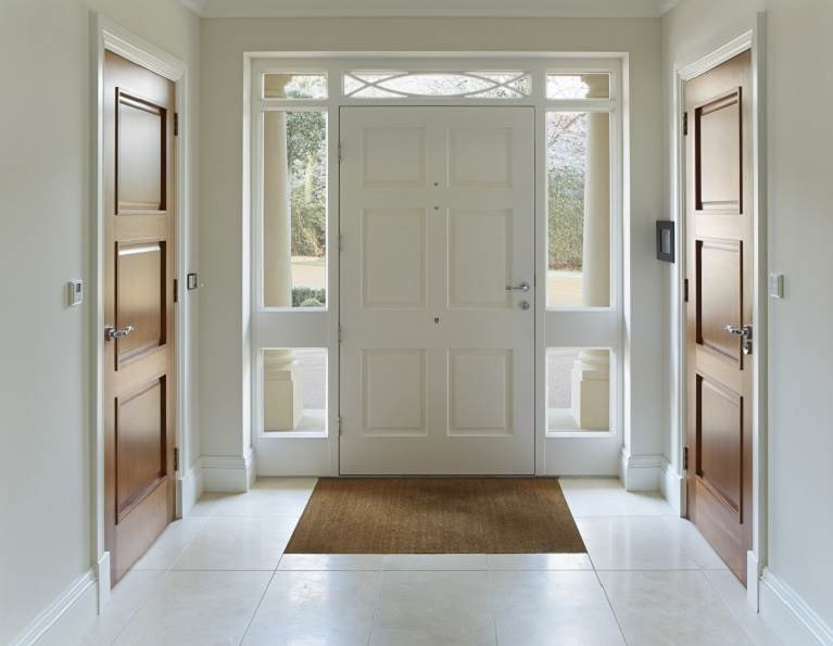 Large foyer with a wooden front door and wooden hallway doors.