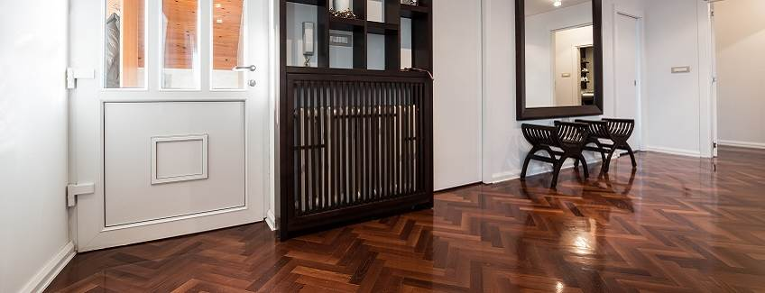 Room with parquet wood floors, a wooden door, and wood furniture.