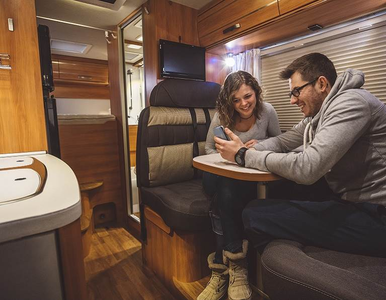 Couple in an RV with wood paneling.