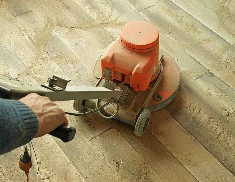 Someone using a floor sanding machine on a hardwood floor.