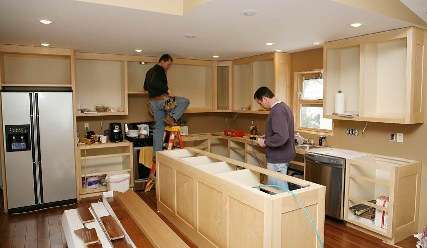Two construction workers finishing off a kitchen.