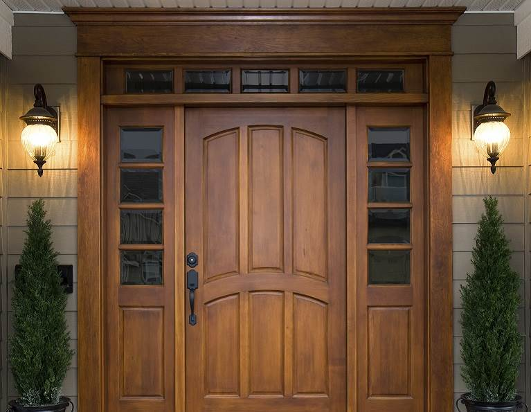 Big wooden front door surrounded by windows representing industrial adhesives from H.B. Fuller.