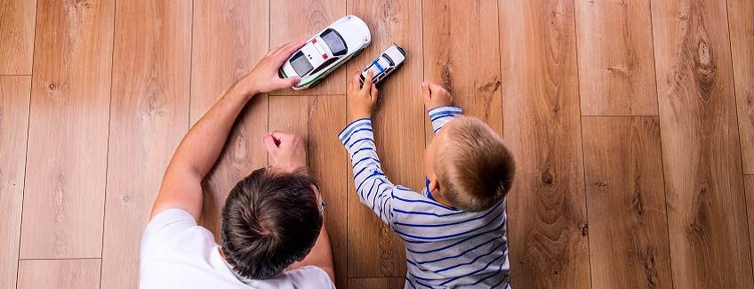 Father and son playing cars on a beautiful engineered wood floor.