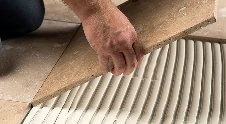 Person gluing down tile.