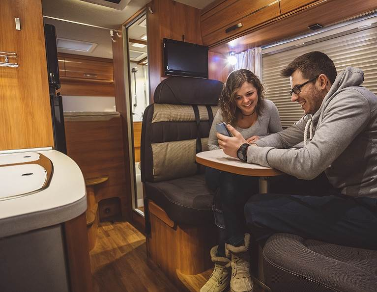 A couple sitting inside an RV with a lot of wood panel lamination.