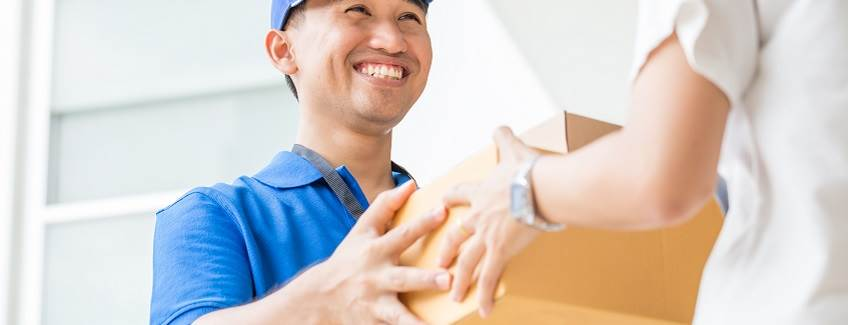 Delivery person with a box manufactured using Close-Sesame adhesive coated solutions for packaging.