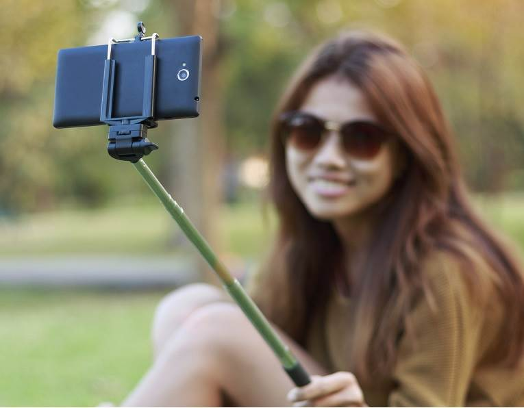 Woman taking a selfie with a cell phone manufactured with adhesives for the electronics module market from H.B. Fuller.