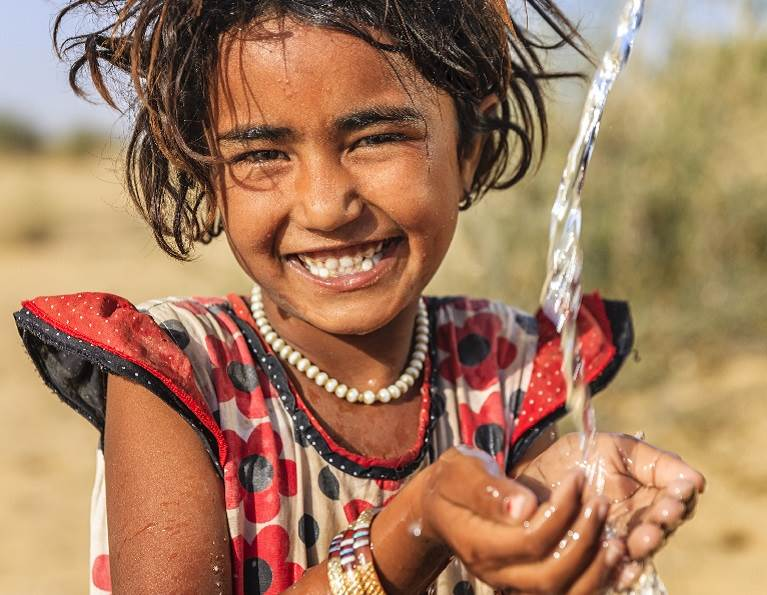 Young girl enjoying fresh water that has been made safe and clean by water filtration.