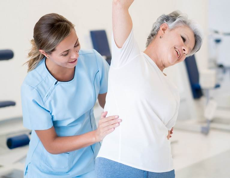 Caretaker and elderly woman doing stretches representing core adhesive solutions from H.B. Fuller for the adult incontinence market.