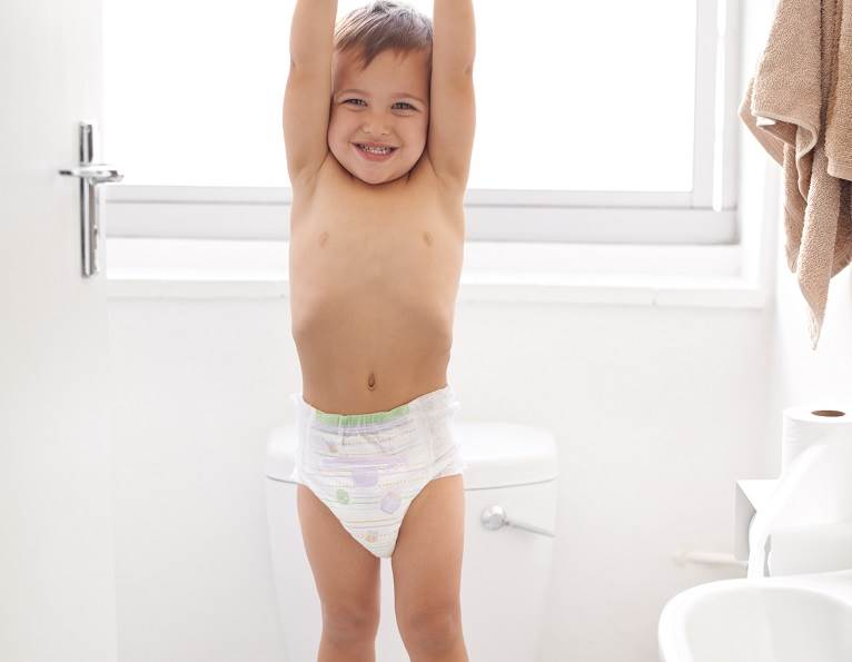 Little boy standing on a toilet in triumph in his diaper demonstrating strong adhesive solutions from H.B. Fuller for elastics in the hygiene and nonwoven market.
