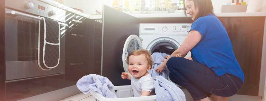 A mom and baby near a washing machine and an oven.