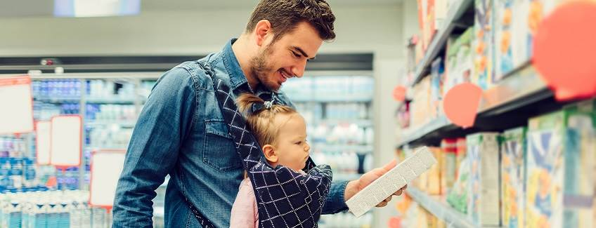 Dad with baby in a grocery store looking at products made with adhesives for the case and carton packaging market by H.B. Fuller.