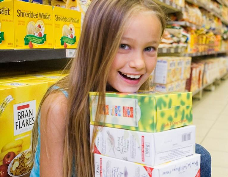 Girl in a grocery store holding boxes sealed with case and carton packaging adhesives from H.B. Fuller.