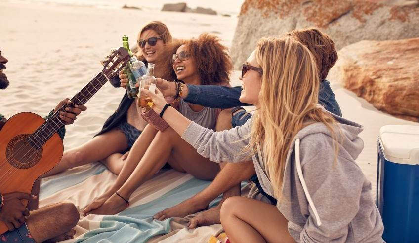 A group of friends on a beach drinking beverages in glass bottles
