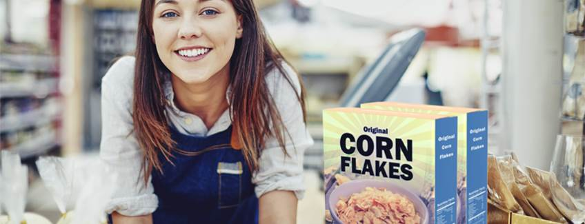 Female cashier at a checkout with a box of cornflakes in the foreground