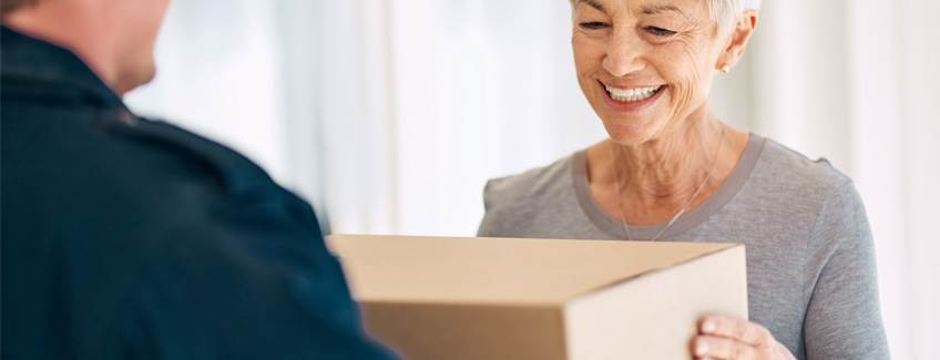 Woman receiving a non-taped cardboard box delivery