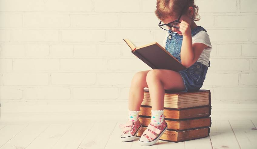 Little girl sitting on a stack of books reading.