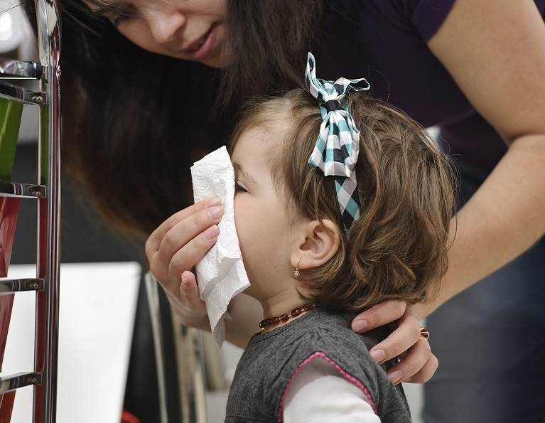 Woman helping a child use a tissue representing adhesives from H.B. Fuller for bath tissue and towel.