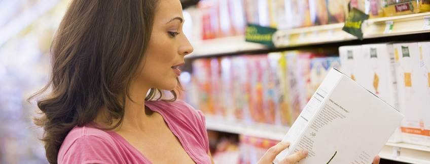 Woman in a grocery store looking at a folding carton.